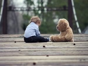 boy-playing-with-teddy-bear-on-wooden-bridge