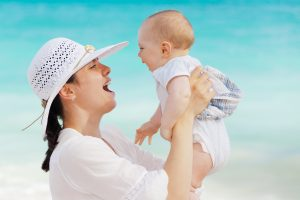 laughing-mother-and-baby-daughter-on-beach