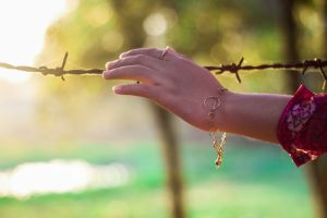 womans-hand-touching-barbed-wire