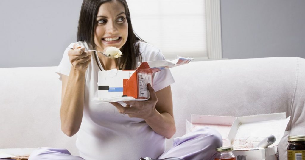 Pregnant-woman-sitting-on-a-couch-and-eating-ice-cream