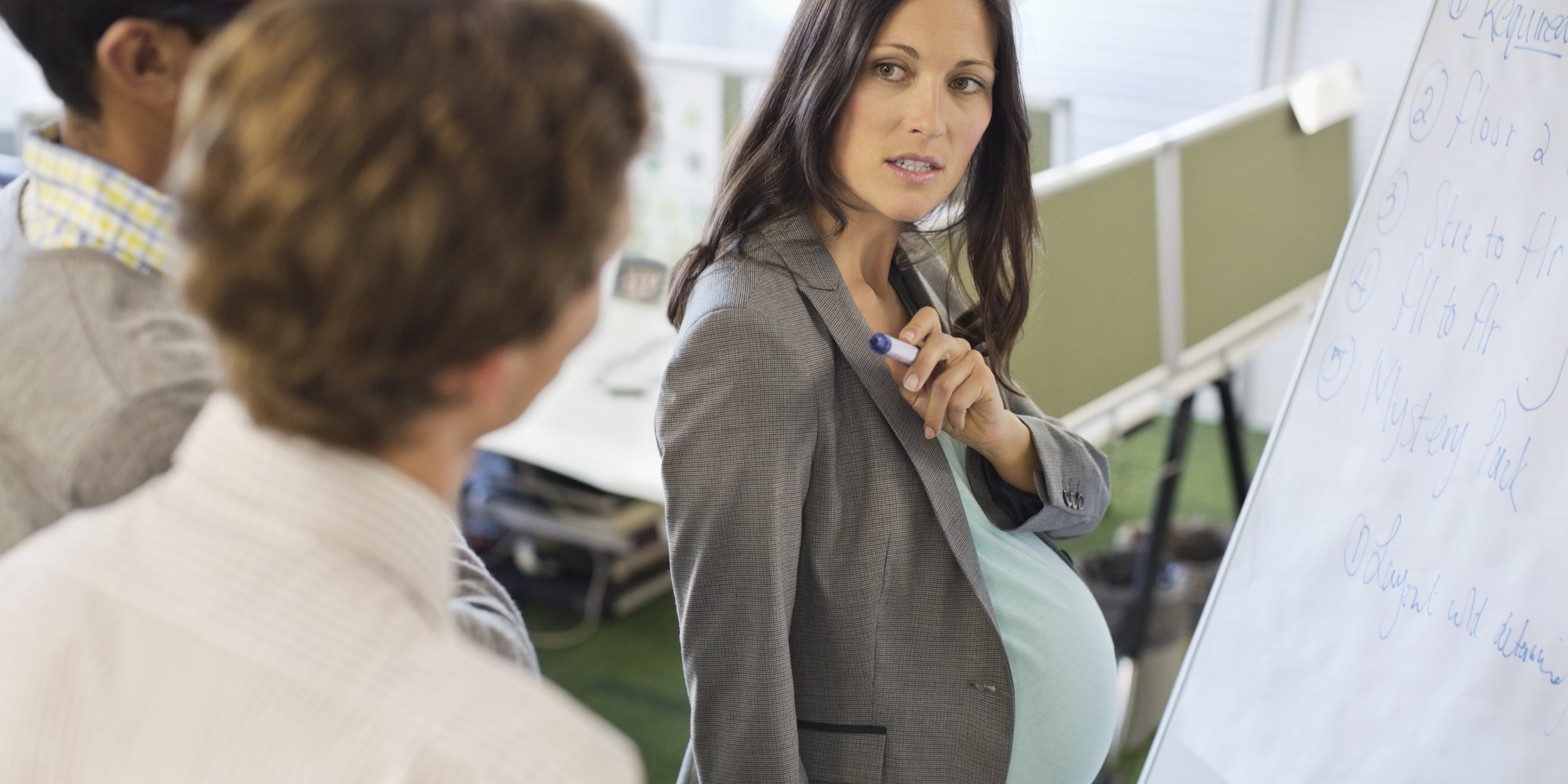 Pregnant businesswoman talking in meeting